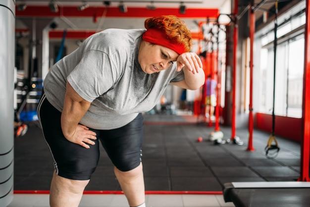 Müde dicke frau nach aktivem training im fitnessstudio. kalorien brennende, fettleibige weibliche person im sportverein Premium Fotos
