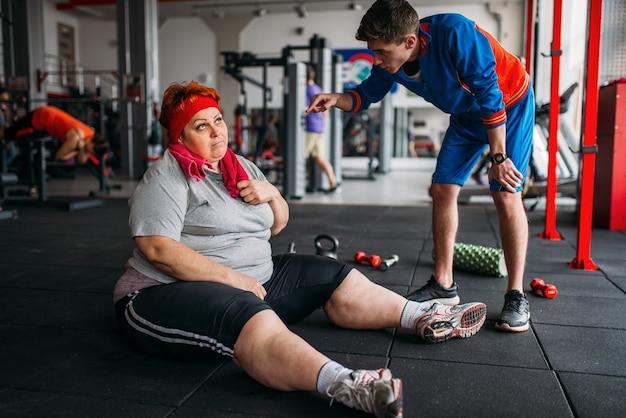 Müde dicke frau sitzt auf dem boden, training mit trainer im fitnessstudio. kalorien brennende, fettleibige weibliche person im sportverein Premium Fotos