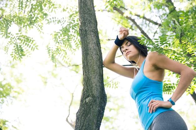 Müde fitnessfrau, die draußen ruht Premium Fotos
