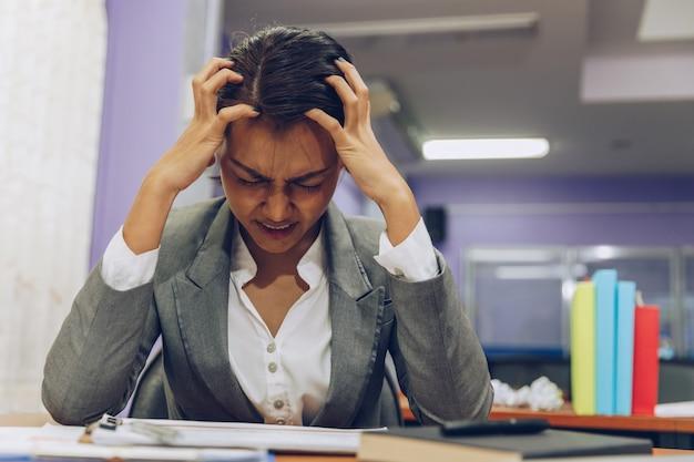 Müde geschäftsfrau mit kopfschmerzen im büro Premium Fotos