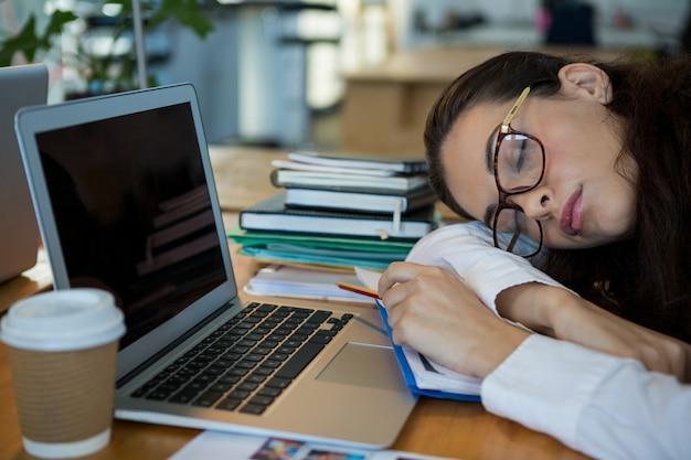 Müde grafikdesignerin, die am schreibtisch schläft Premium Fotos