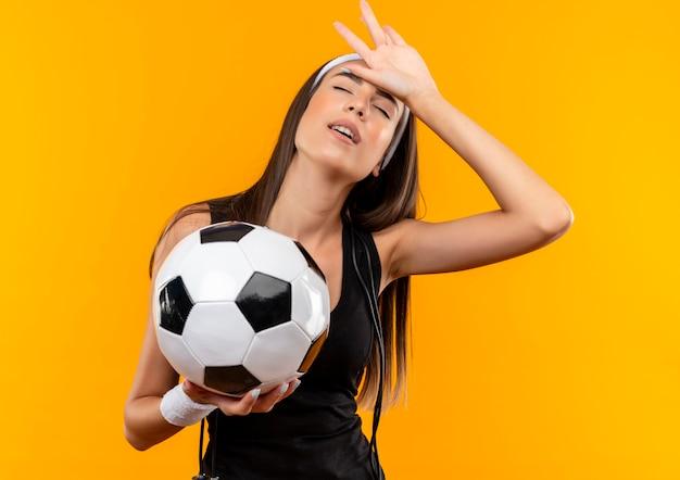 Müde junge hübsche sportliche mädchen, die stirnband und armband halten fußball halten hand auf den kopf mit geschlossenen augen mit springendem seil um ihren hals lokalisiert auf orange raum Kostenlose Fotos