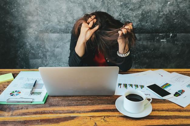 Müde und kopfschmerzengeschäftsfrau im büro unter verwendung des laptops und analysieren von investitionsdiagrammen auf dokumentenpapier Premium Fotos