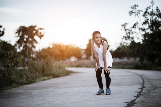 Müder eignungsfrauenläufer, der eine pause nach dem schnellfahren macht Kostenlose Fotos