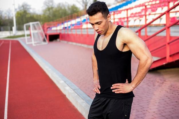 Müder erschöpfter männlicher athlet, der auf stadion steht Kostenlose Fotos