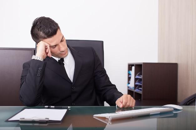 Müder geschäftsmann, der im büro arbeitet Premium Fotos