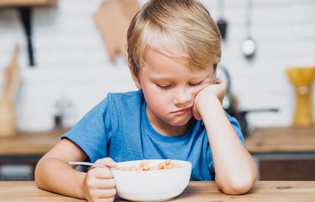 Müder junge, der versucht, sein getreide zu essen Kostenlose Fotos