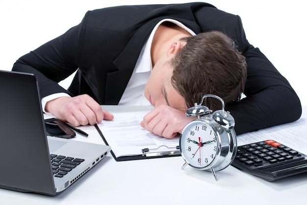 Müder junger geschäftsmann, der nahe bei seinem laptop schläft. Premium Fotos
