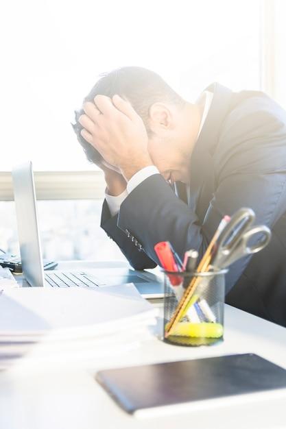 Müder junger geschäftsmann mit laptop an seinem arbeitsplatz Kostenlose Fotos