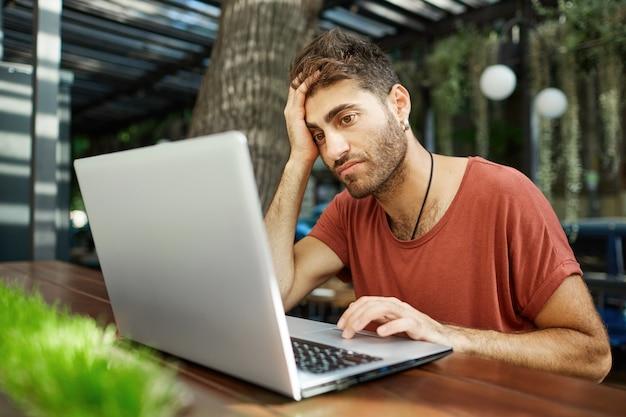 Müder junger hübscher mann, der mit laptop im straßencafé sitzt, fern arbeitet oder mit park-wlan studiert Kostenlose Fotos