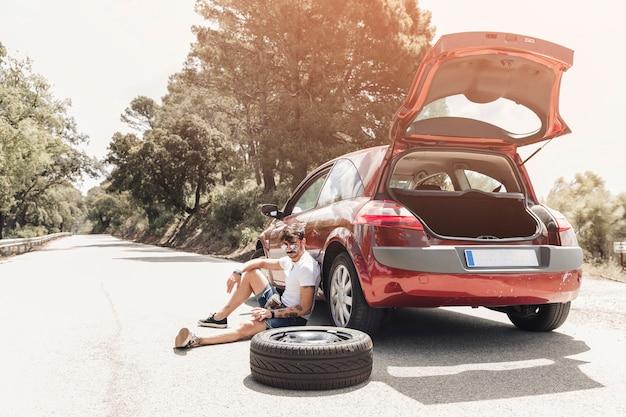 Müder junger mann, der nahe dem aufgegliederten auto auf straße sitzt Kostenlose Fotos