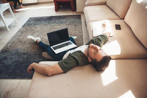 Müder kaukasischer mann, der auf boden mit einem laptop liegt, der einschlafen, nachdem er online arbeitet Premium Fotos