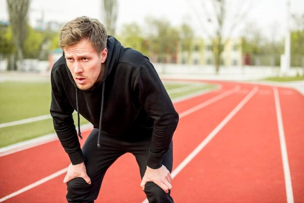 Müder männlicher athlet, der auf rennstrecke steht Kostenlose Fotos