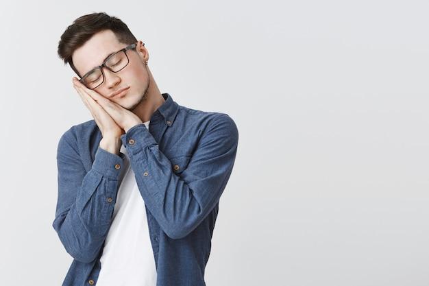 Müder student in gläsern, der sich mit geschlossenen augen auf handflächen stützt und schläft Kostenlose Fotos