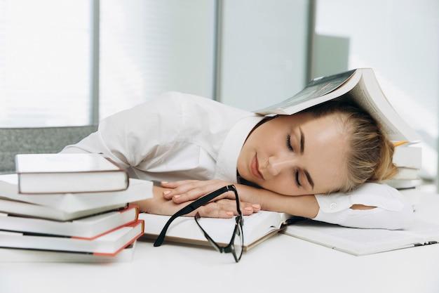 Müder student schläft auf den büchern in der bibliothek Premium Fotos