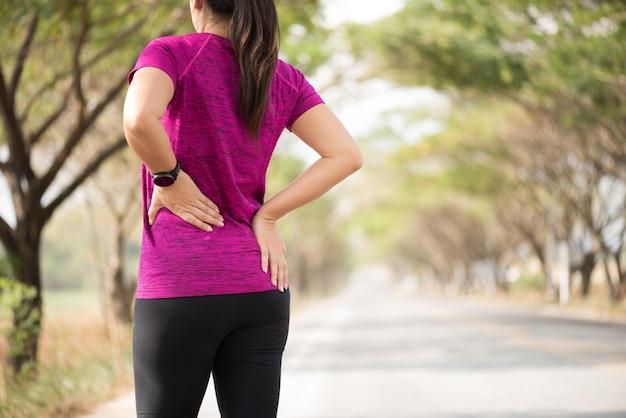 Müdes mädchen fühlen schmerz auf ihrem rücken und hüfte beim trainieren, gesundheitswesenkonzept. Premium Fotos