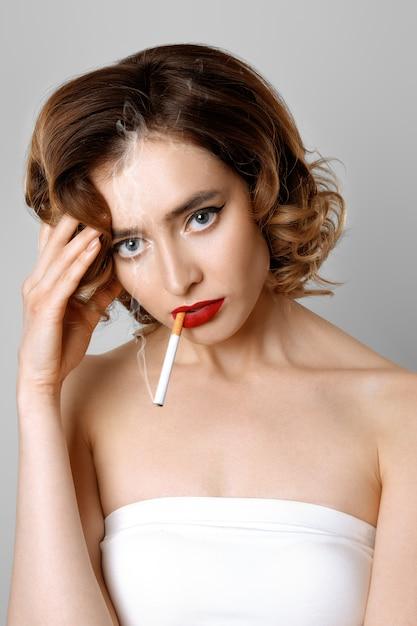 Müdes schönheitsmodell mit rauchender sigarette der kopfschmerzen Premium Fotos