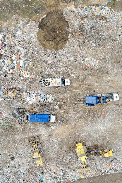 Müllhaufen in müllkippe oder mülldeponie. muldenkipper und bagger entladen abfälle. Premium Fotos