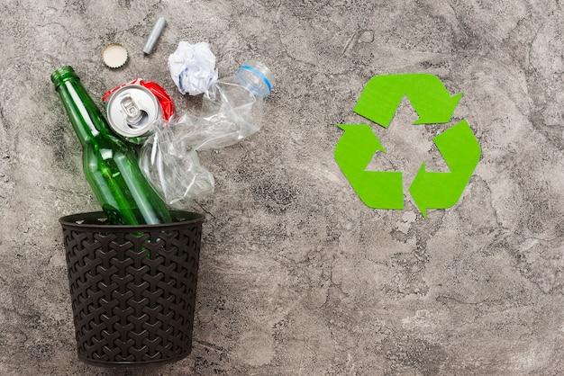 Mülltonne mit müll neben recycling-logo Kostenlose Fotos