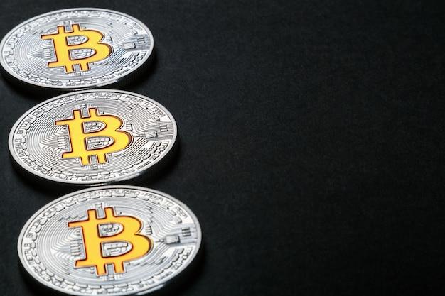 Münzen der bitcoin-kryptowährung auf schwarz Premium Fotos