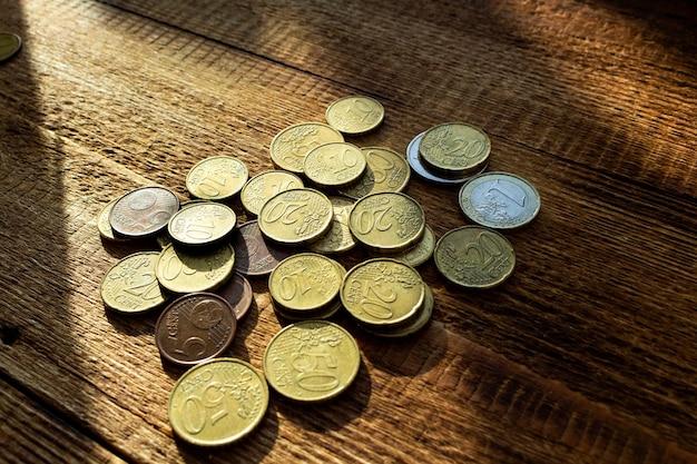 Münzen im sonnenstrahl auf dem hölzernen hintergrund Premium Fotos