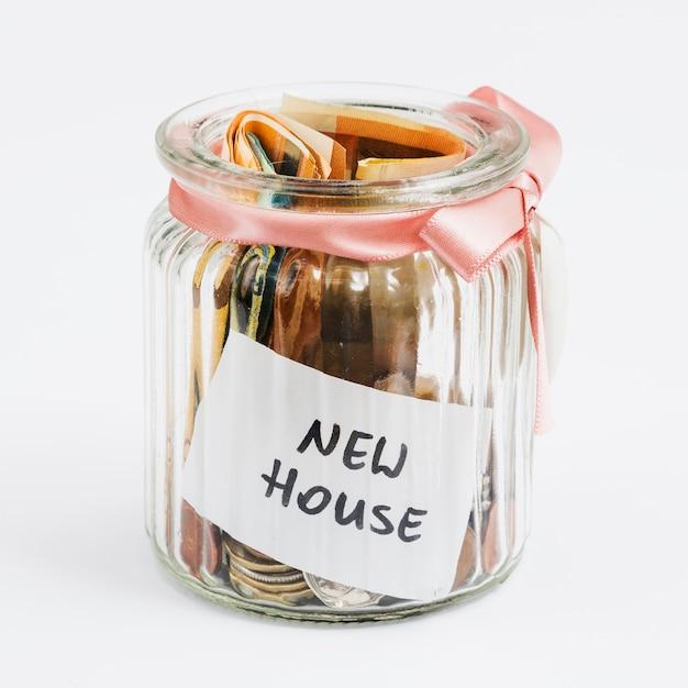 Münzen und euroanmerkungen im glas, das mit rosa band verziert wurde, sammelten für neues haus Kostenlose Fotos