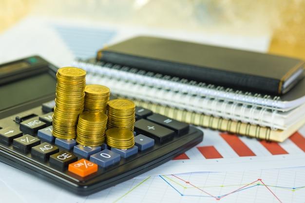 Münzenstapel und finanzielles millimeterpapierblatt mit taschenrechner auf arbeitstisch, unternehmensplanungsvision und finanzanalysekonzept. Premium Fotos
