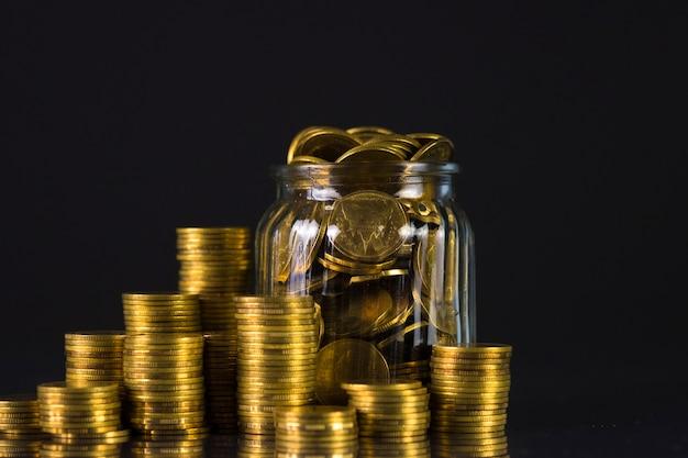 Münzenstapel und goldmünzgeld im glasgefäß auf dunklem hintergrund Premium Fotos