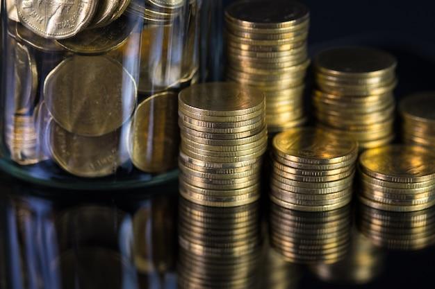 Münzenstapel und goldmünzgeld im glasgefäß Premium Fotos