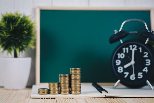 Münzenstapel und wecker mit grüner tafel Premium Fotos