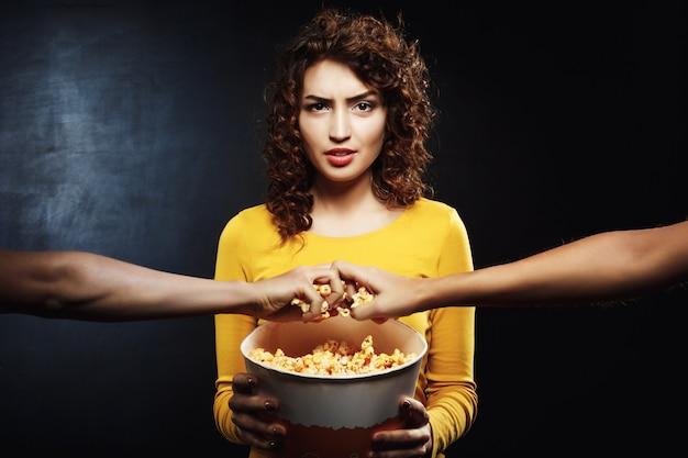 Mürrische frau hält popcorn-eimer und will nicht teilen Kostenlose Fotos
