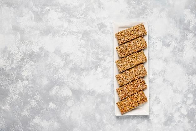Müsliriegel. gesunder süßer nachtischsnack. sesam, erdnuss, sonnenblume in honig. gozinaki ist ein georgisches nationalgericht, orientalisch süß. draufsicht auf beton Kostenlose Fotos