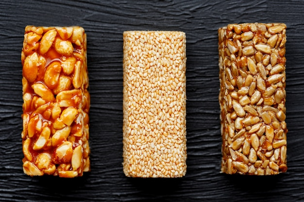 Müsliriegel mit erdnüssen, indischem sesam und sonnenblumensamen auf einem schneidebrett auf einer dunklen steintabelle. von oben betrachten. drei verschiedene bars Premium Fotos