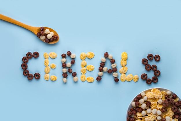 Müslischüssel und löffel auf einer blauen brandung. glasierte schokoladenbällchen, ringe und cornflakes für ein gesundes trockenes frühstück. getreide-konzept Premium Fotos