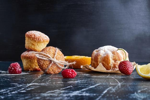 Muffins isoliert auf blauer oberfläche. Kostenlose Fotos