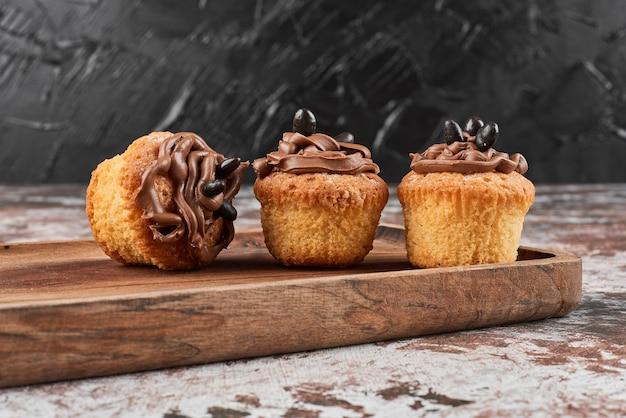 Muffins mit kakaocreme auf einem holzbrett. Kostenlose Fotos