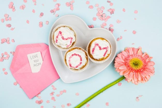 Muffins mit mutterwort auf platte nahe blume und umschlag mit tag zwischen konfetti Kostenlose Fotos