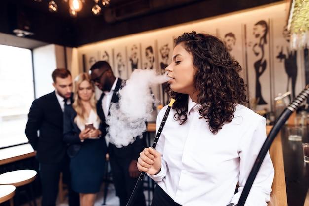 Mulattin raucht eine shisha an der bar. Premium Fotos