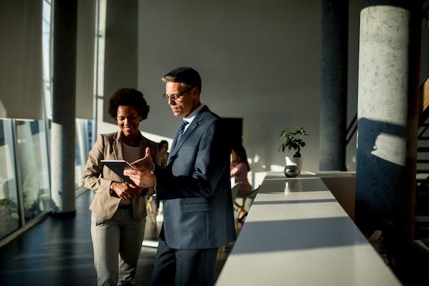 Multiethnische geschäftsleute, die digitales tablet verwenden, während sie im büro stehen Premium Fotos
