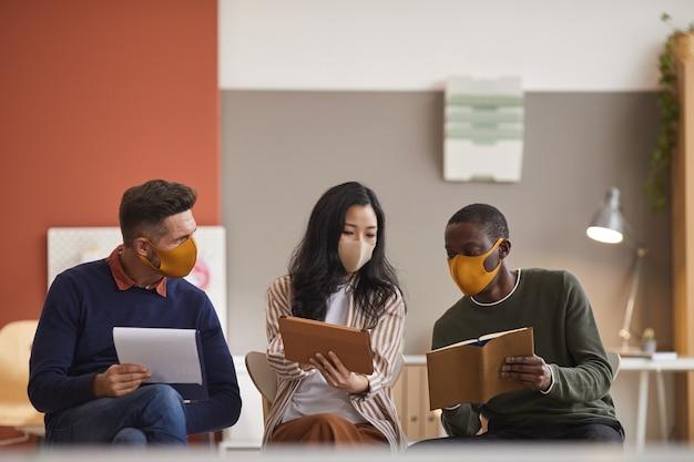 Multiethnische gruppe von drei geschäftsleuten, die gesichtsmasken tragen, während sie das projekt im büro besprechen Premium Fotos