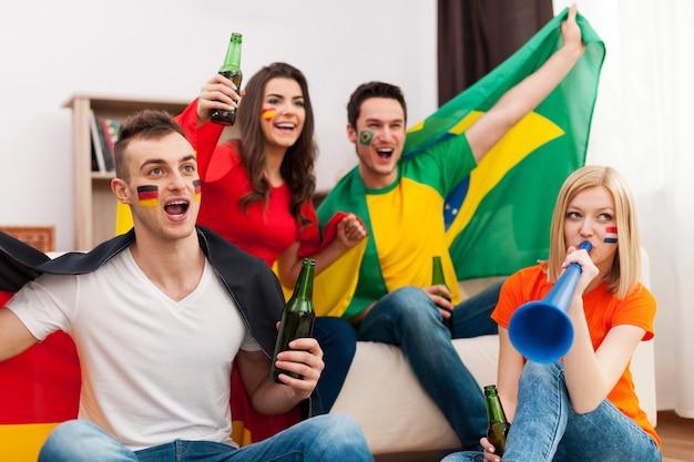 Multiethnische gruppe von menschen, die fußballspiel jubeln Kostenlose Fotos