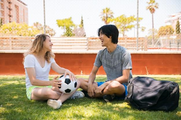 Multiethnische jugendfreunde, die am fußballplatz sitzen Kostenlose Fotos