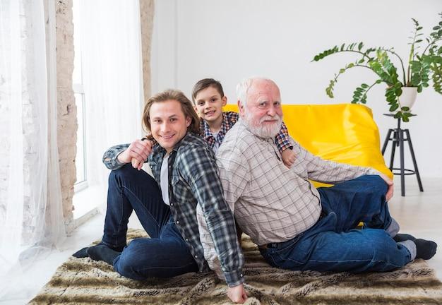 Multigenerationale männer, die zu hause auf teppich sitzen Kostenlose Fotos