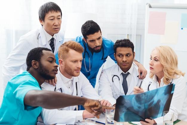 Multinationale ärzte untersuchen das röntgenbild des patienten. Premium Fotos