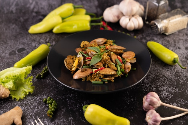 Muscheln gebratenes currypulver auf einem schwarzen teller. Kostenlose Fotos