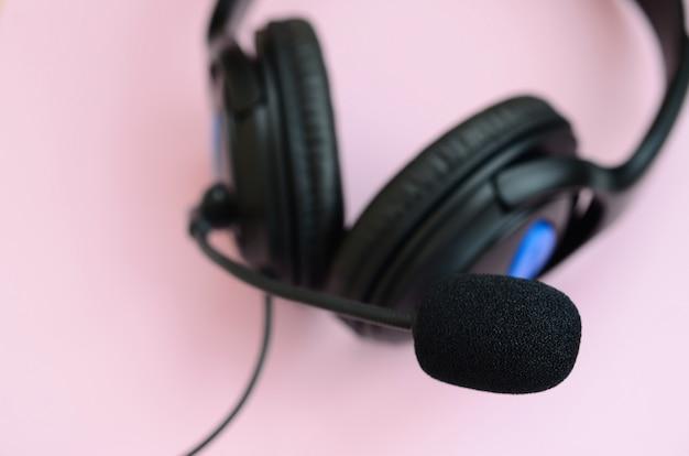 Musik hörendes konzept. schwarze kopfhörer liegt auf rosa hintergrund Premium Fotos