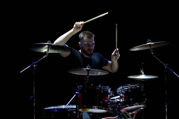 Musik, leute, musikinstrumente und unterhaltungskonzept - männlicher musiker mit den trommelstöcken, die trommeln und becken am konzert oder am studio spielen Premium Fotos