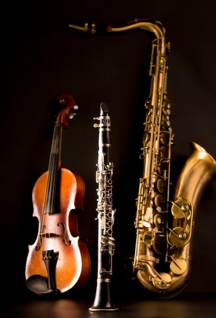 Musik sax tenorsaxophon violine und klarinette in schwarz Premium Fotos