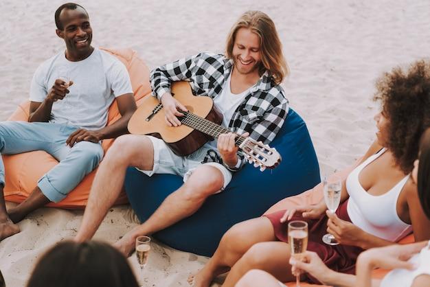 Musiker, der gitarre auf strand für freunde spielt Premium Fotos