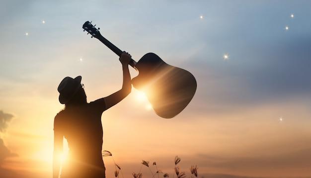 Musiker, der in der hand gitarre des schattenbildes auf sonnenuntergangnaturhintergrund hält Premium Fotos